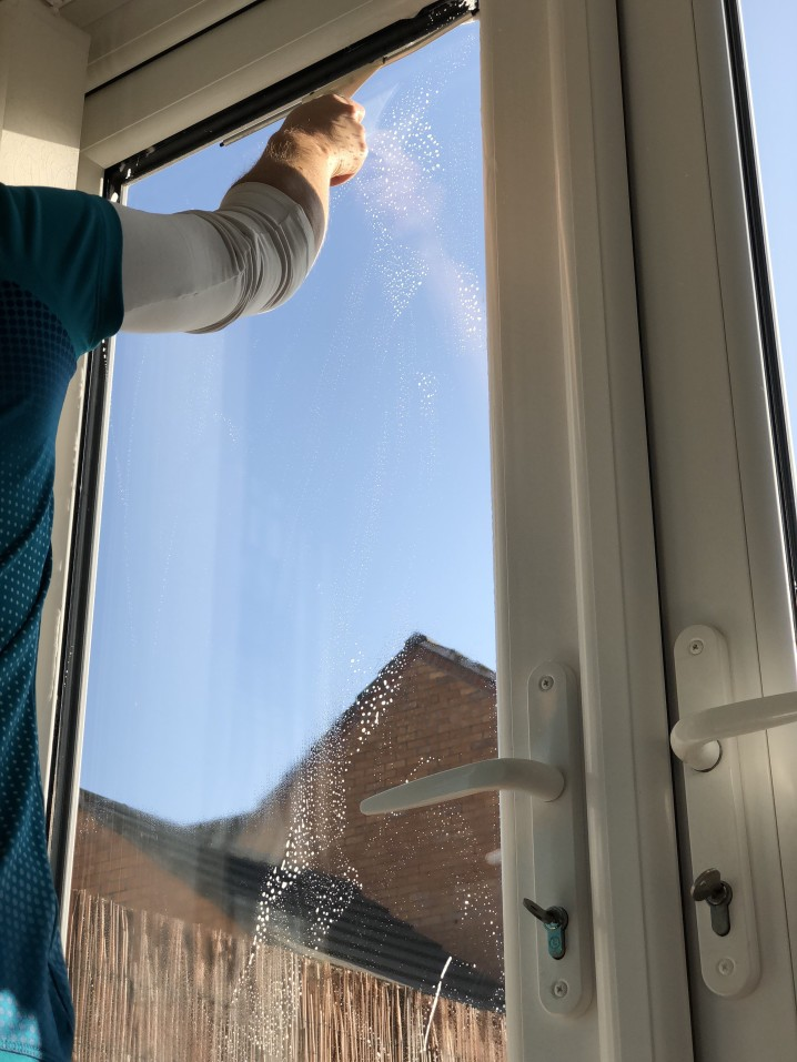 Our Glass Cleaner of Boise man washing windows and using a squeegee